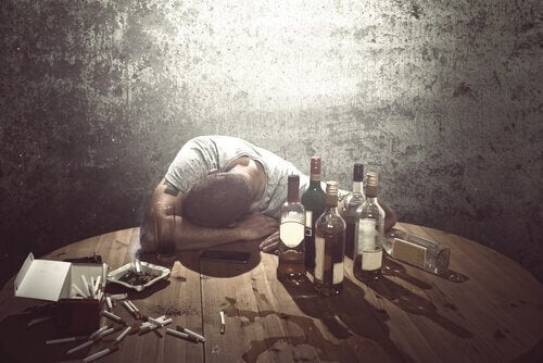 Mann schläft am Tisch mit Flaschen und Zigaretten.