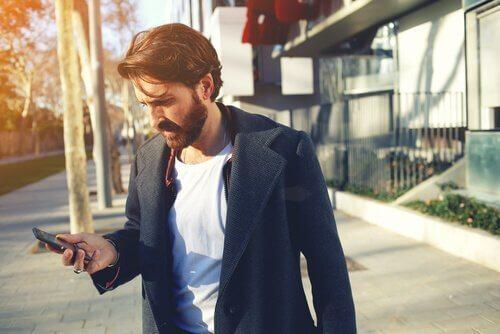 Ein Mann liest eine Textnachricht auf dem Bürgersteig.