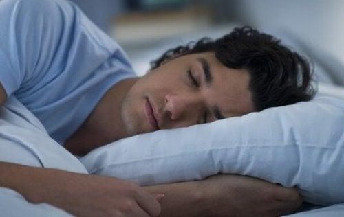 Ein Mann schläft im Bett.