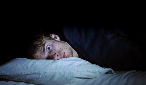 Ein Mann liegt mit weit geöffneten Augen im Bett.