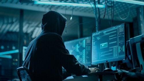 Ein Mann sitzt vor einem Computerbildschirm in einem dunklen Raum.