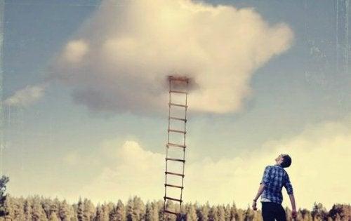 Ein Mann steht vor einer Leiter, die in einer Wolke verschwindet.