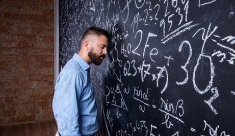 Erschöpfter Lehrer lehnt seinen Kopf an die vollgeschriebene Tafel.