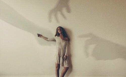 Frau mit Schatten, die nach ihr greifen