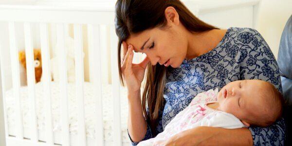 Eine junge Mutter hält ihr Baby auf dem Arm, während sie sich mit einer Hand an die Stirn greift.