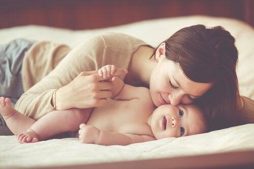 Eine junge Mutter umarmt glücklich ihr Baby.