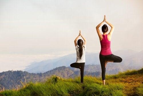 Eine Mutter und ihr Kind stehen auf einem Berg, während sie eine Yoga-Übung machen.