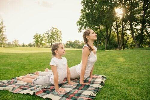 Eine Mutter und ihr Kind sind im Park und machen Yoga auf einer Decke.