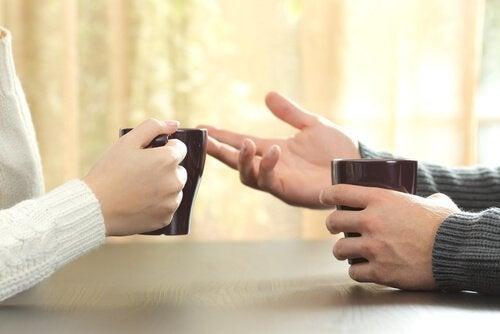 Zwei Menschen diskutieren, während sie einen Kaffee trinken.