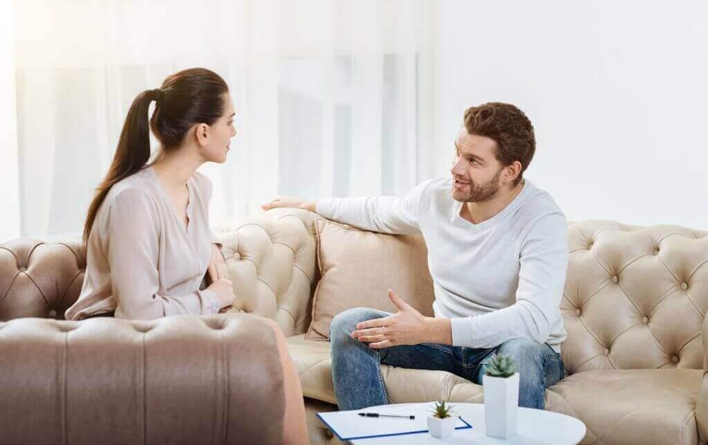 Ein Paar sitzt auf der Couch und spricht miteinander