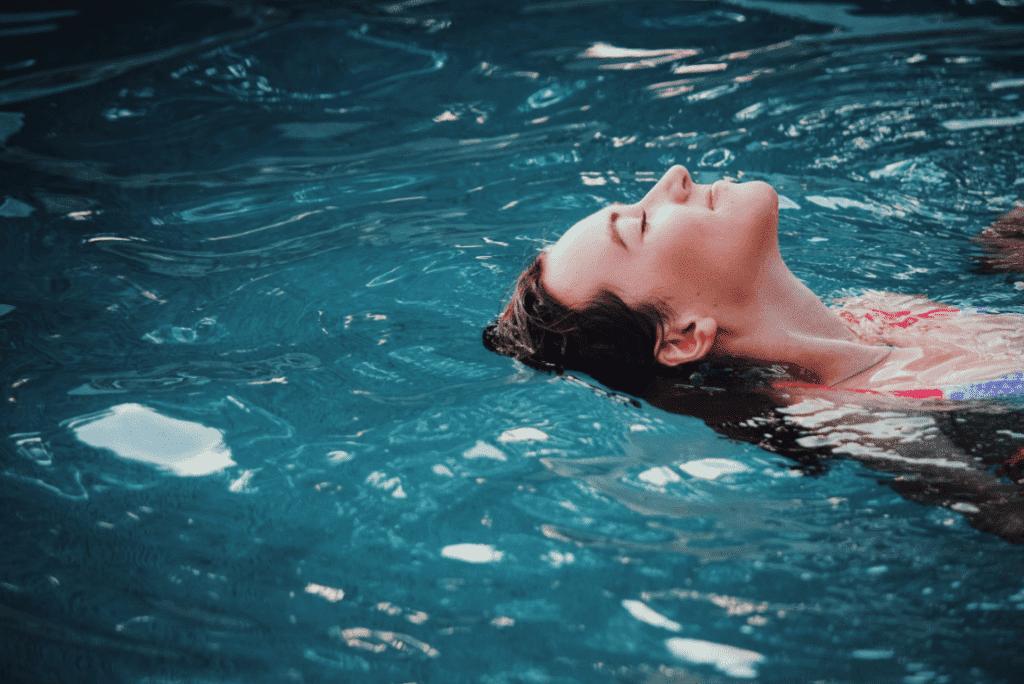 Frau treibt mit einem Lächeln im Gesicht auf der Wasseroberfläche