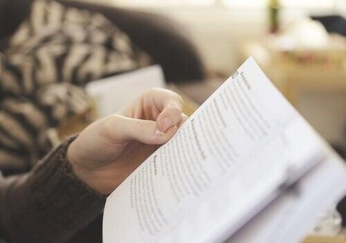 Eine Person sitzt auf einer Couch und liest ein Buch.