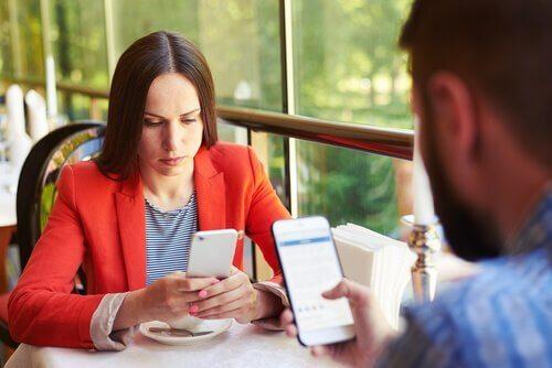 Ein Paar ist im Restaurant beim Essen, beide schauen aber auf ihr Handy.