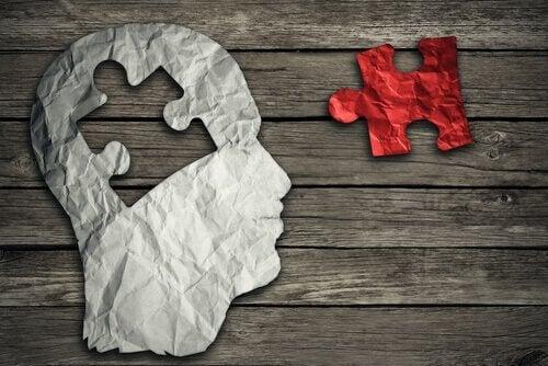 Ein rotes Puzzelteil auf einem Tisch und ein menschlicher Kopf aus Pappe, in den das Puzzleteil zu passen scheint.