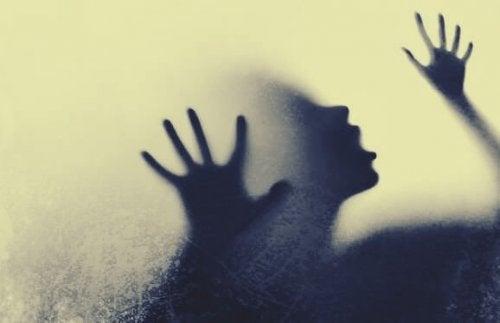 Ein Schatten einer Frau, die Hilfe sucht, hinter einem Milchglas