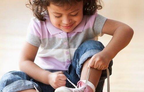 Selbstständiges Kind bindet sich die Schuhe.