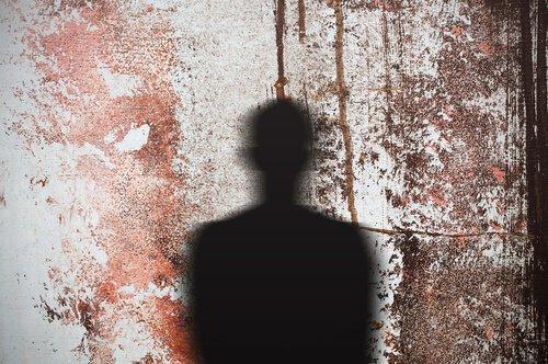 Schatten eines Mannes, der auf eine mit rot gesprengte Wand fällt