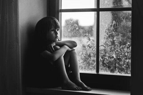 Kind, das traurig bei einem Fenster sitzt