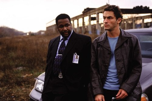 """""""The Wire"""" - Zwei Männer sitzen auf einer Autohaube und unterhalten sich."""