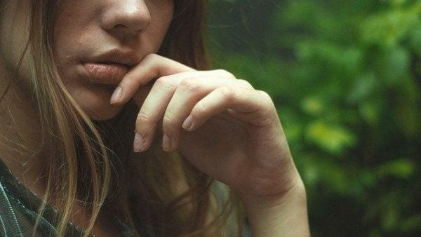 Beim Zweifeln nimmt eine Frau ihre linke Hand an den Mund.