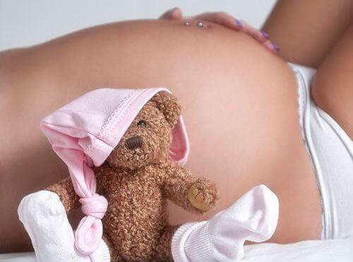 Eine Frau liegt auf einem Bett und zeigt ihren Babybauch.