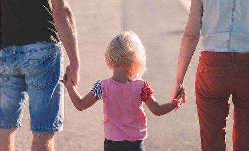 Eltern halten ihr Kind an den Händen.