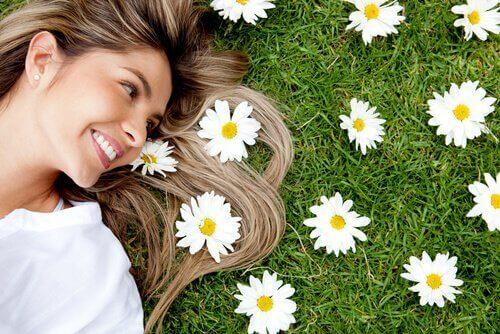Frau, die fröhlich ist und lächelt, liegt auf einer Wiese voller Blumen