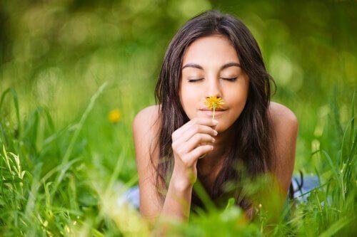 Eine Frau liegt im Gras und riecht an einem Löwenzahn.