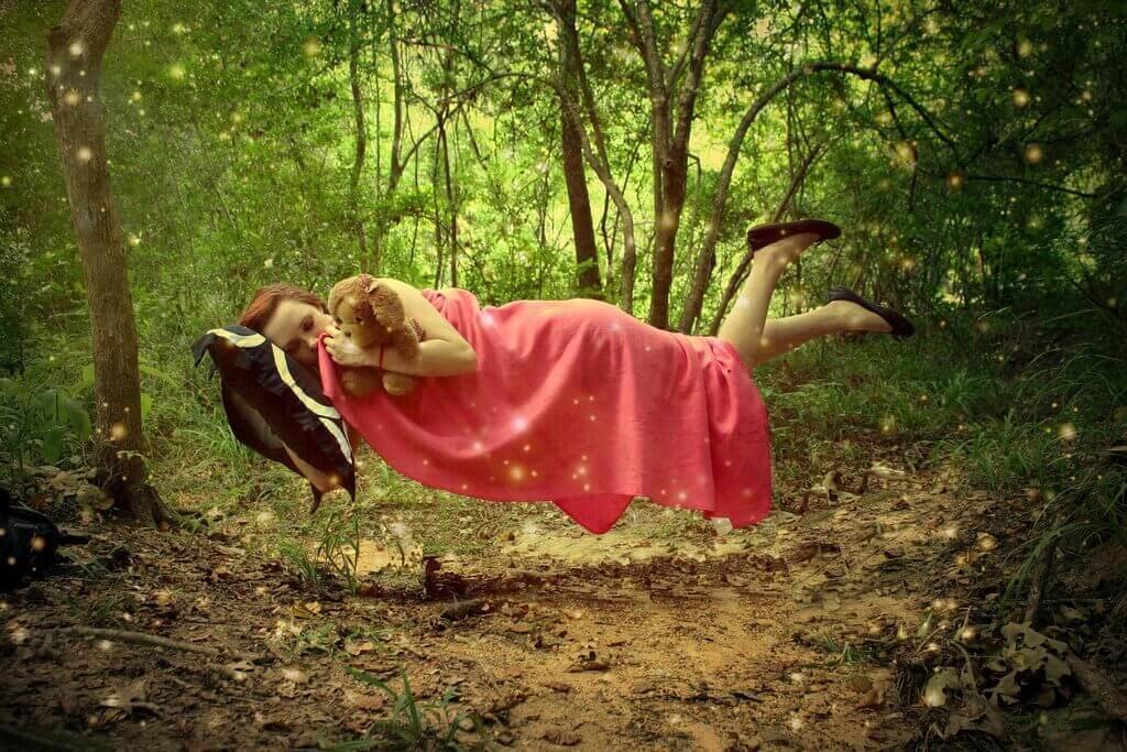 Schwebende Frau, die mit ihrem Stofftier kuschelt
