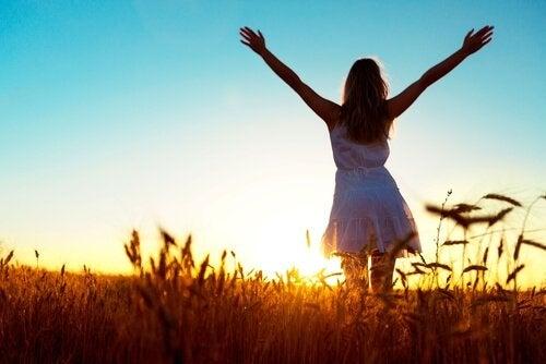 Glückliche Frau, die ihre Hände dem Sonnenuntergang entgegenstreckt