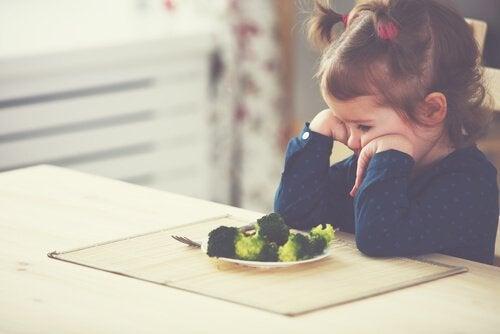 Ein kleines Mädchen will kein Gemüse essen.