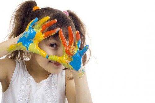 Ein Mädchen hält seine Hände voller Fingerfarbe glücklich in die Kamera.