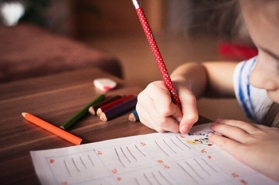 Ein Mädchen schreibt mit einem Buntstift.