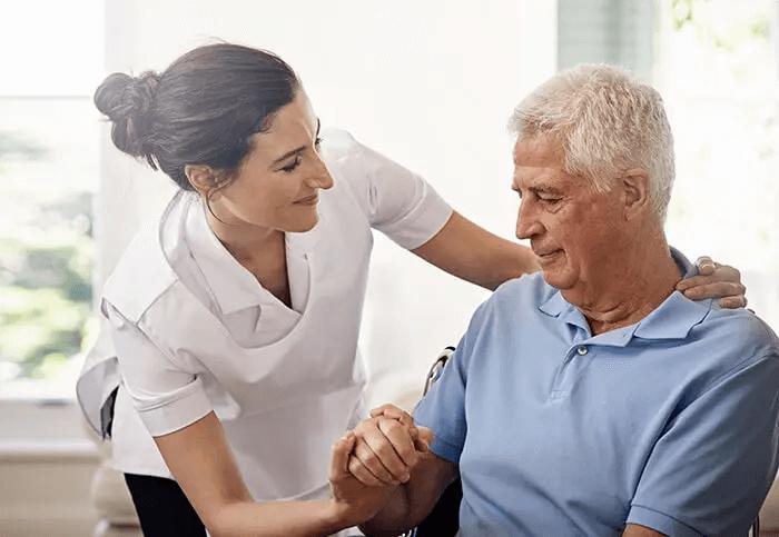 Mann mit Ataxie wird von einer Pflegerin betreut