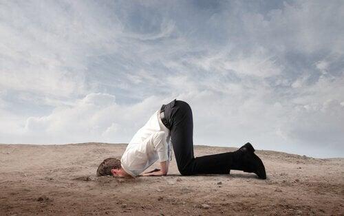 Ein Mann steckt den Kopf in den Sand.