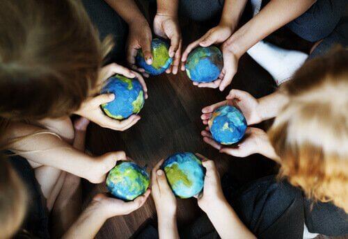 Menschen, die kleine Weltkugeln in der Hand halten