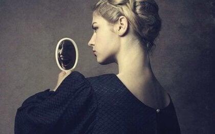 Narzisstische Frau blickt in den Spiegel.