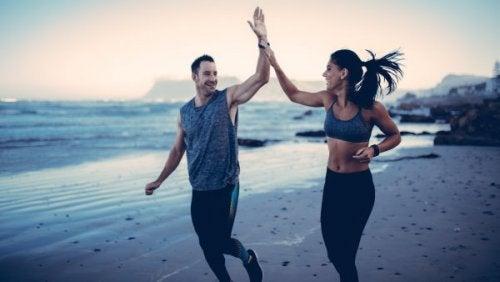 Ein Mann und eine Frau joggen entspannt an einem Strand und haben Spaß.