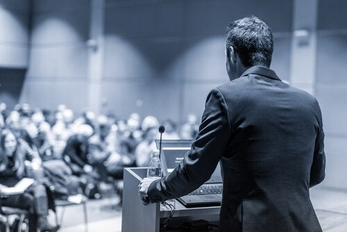 Ein Professor steht am Rednerpult, während er seine Vorlesung hält.