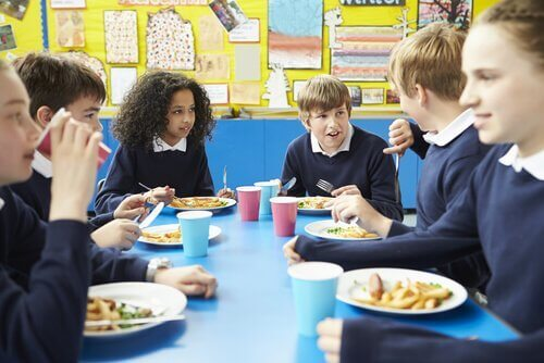 In der Schulcafeteria können Kinder Tischmanieren lernen.