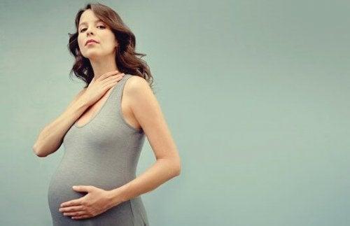 Eine schwangere Frau präsentiert stolz ihren Babybauch.