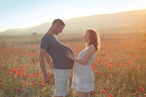 Ein schwangerer Mann und seine schwangere Frau stehen in einem Mohnblumenfeld.