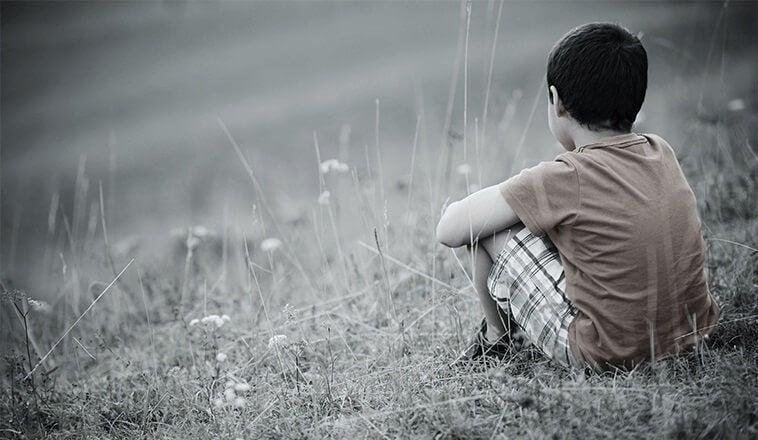 Trauriger Junge sitzt allein auf einer Wiese.