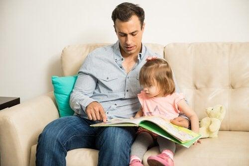 Ein Vater liest mit seiner Tochter.