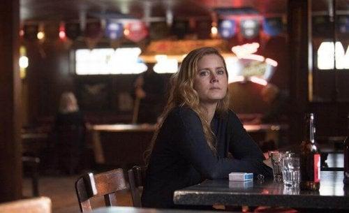 """Camille, Hauptcharakter in der Serie WSharp Objects"""", sitzt allein in einer Bar."""