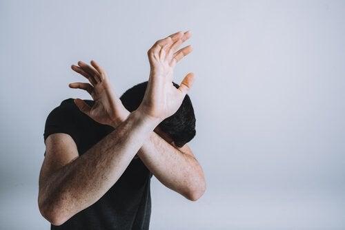 Ein ängstlicher Mann schirmt sich mit seinen Armen ab.