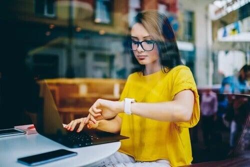 Frau arbeitet am Rechner und schaut auf die Uhr