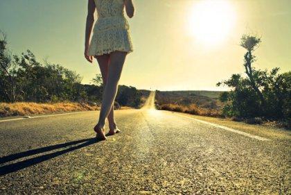 Frau geht auf einer Straße Richtung Horizont