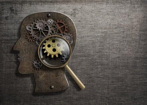 Der Kopf einer Person, unter einer Lupe betrachtet, der die Mechanismen des Geistes zum Vorschein kommen lässt