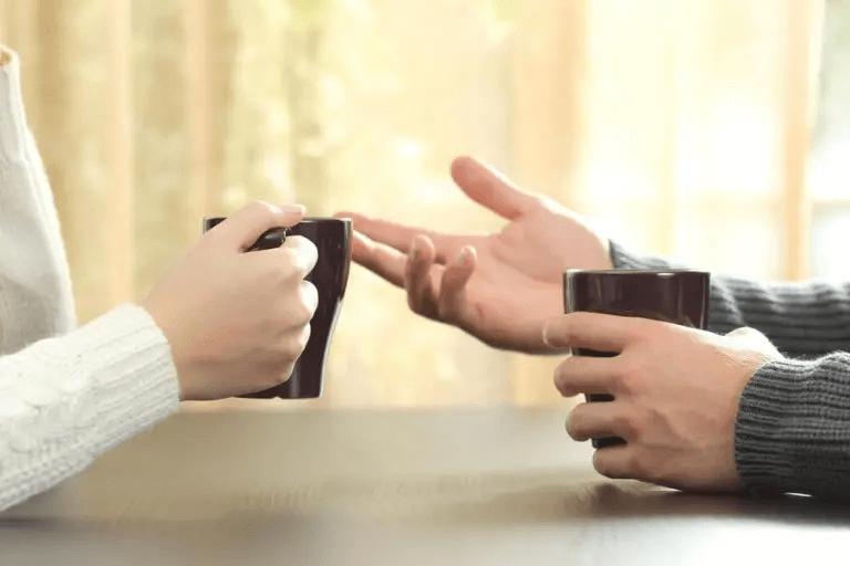 Zwei Menschen unterhalten sich bei einer Tasse Kaffee.